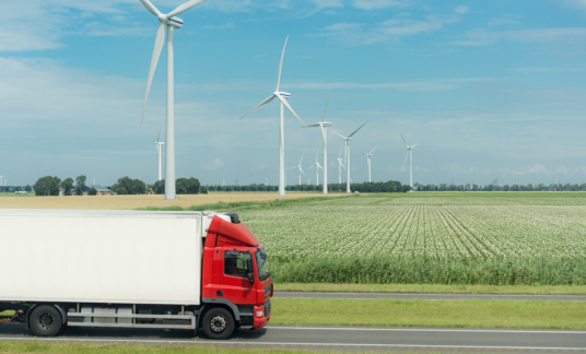 flat netherland  with truck, wind turbines and blooming crop