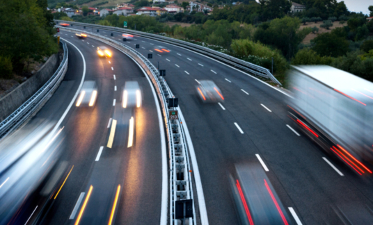 Traffic On Highway At Dusk, With Blurred Cars And Trucks