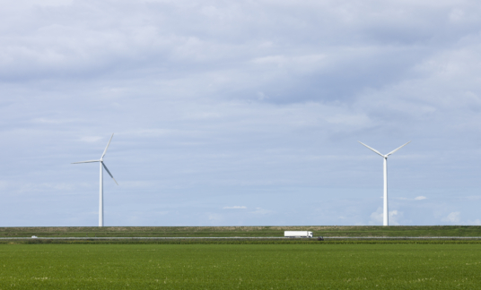 Dual Wind Turbines Spinning Above Highway