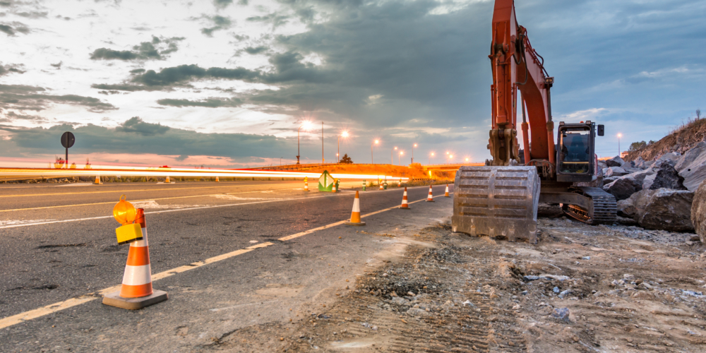 Works of extension of a road with excavator and delimited by safety cones