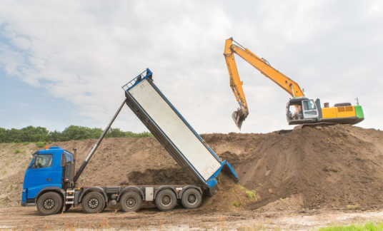 Truck and excavator together build a sound barrier