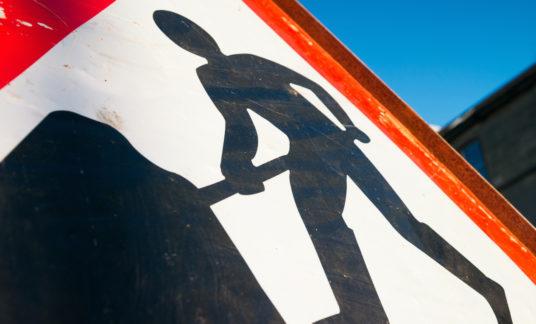 Men At Work sign closeup